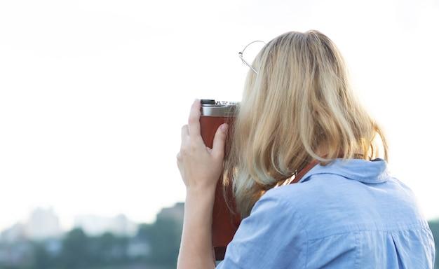 빈티지 필름 카메라에 사진을 찍고 파란 드레스에 젊은 hipster 젊은 여성 사진 작가. 빈 공간