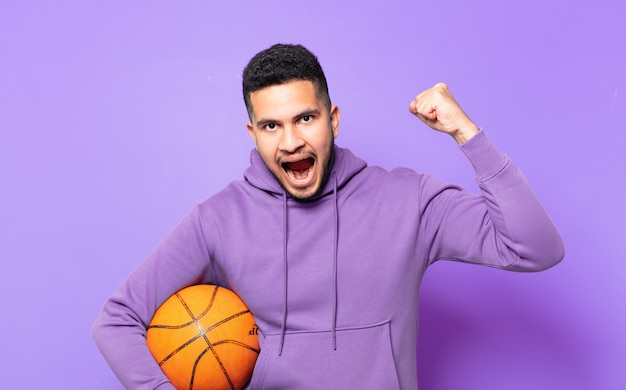 성공적인 승리를 축하하고 농구 공을 들고 젊은 히스패닉 운동 남자