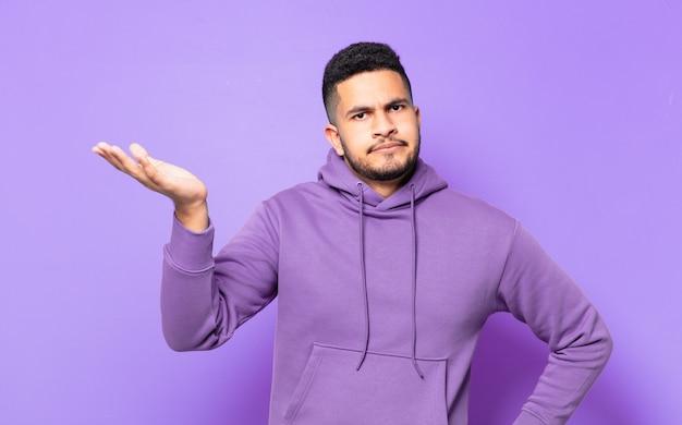 Молодой человек латиноамериканского спортсмена сомневается или неуверенно выражает свое мнение
