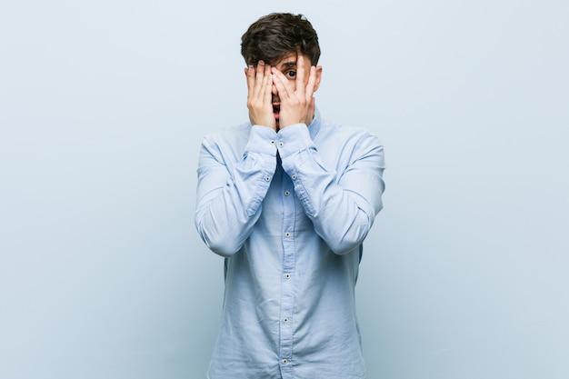 Молодой испаноязычный деловой человек моргает сквозь пальцы испуганно и нервно.