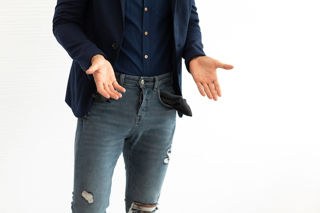 Young hispanic business man freelancer showing his empty pockets standing on white background.