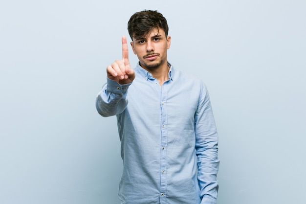 Young hispanic business man showing number one with finger.