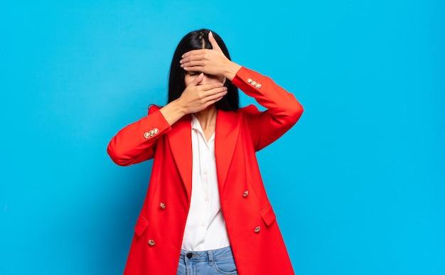 Молодая латиноамериканская коммерсантка закрыла лицо обеими руками, говоря «нет» камере! отказ от фотографий или запрет на фотографии