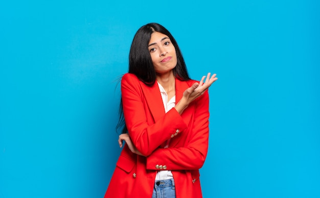 Молодая латиноамериканская бизнесвумен чувствует себя смущенной и невежественной, гадая над сомнительным объяснением или мыслью