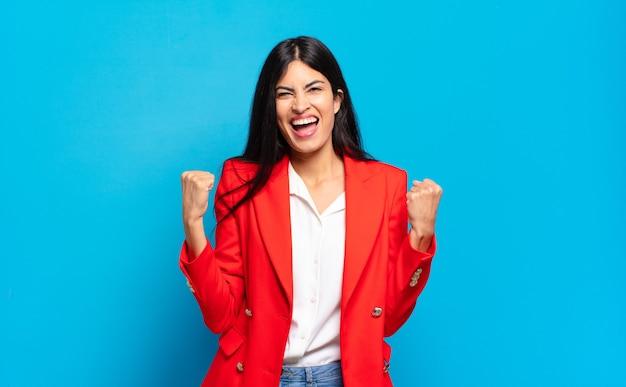 Молодая латиноамериканская деловая женщина чувствует себя счастливой, позитивной и успешной, празднует победу, достижения или удачу