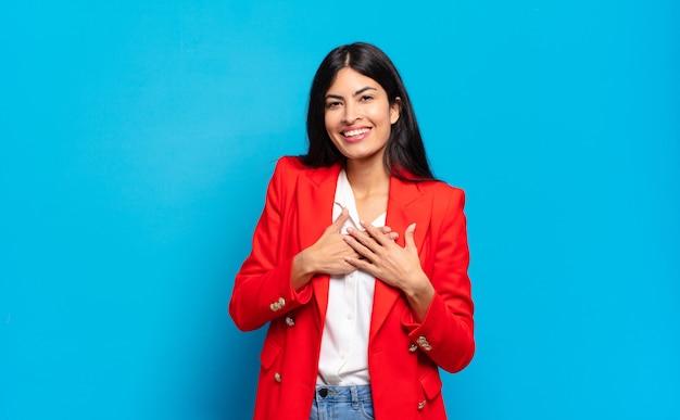 Молодая латиноамериканская деловая женщина чувствует себя романтичной, счастливой и влюбленной, весело улыбается и держится за руки близко к сердцу