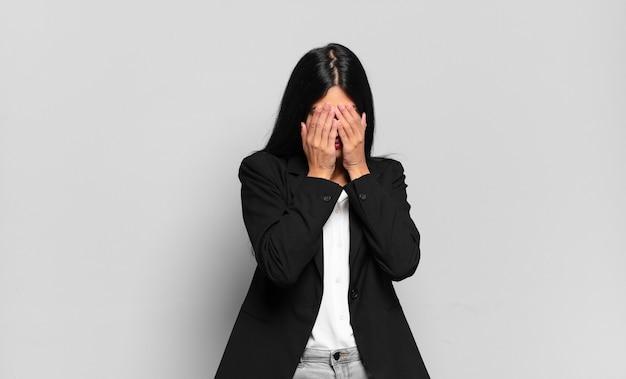 젊은 히스패닉 여성 사업가는 슬프고, 좌절하고, 긴장하고, 우울하고, 두 손으로 얼굴을 가리고, 울고 있다