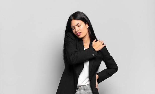 Молодая бизнесвумен-латиноамериканка чувствует усталость, стресс, тревогу, разочарование и депрессию, страдает от боли в спине или шее