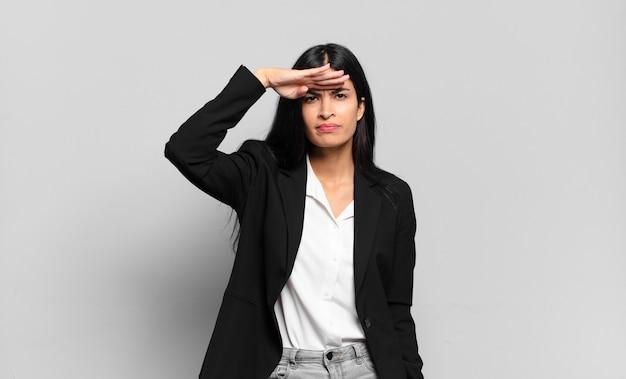 Молодая латиноамериканская деловая женщина выглядит сбитой с толку и удивленной, с рукой над лбом смотрит вдаль, смотрит или ищет