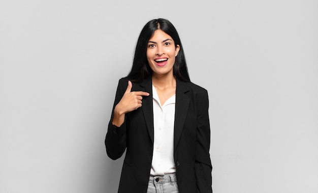 Young hispanic businesswoman looking happy, proud and surprised, cheerfully pointing to self, feeling confident and lofty