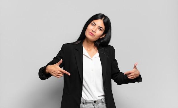 Молодая латиноамериканская бизнесвумен выглядит гордой, высокомерной, счастливой, удивленной и удовлетворенной, указывая на себя, чувствуя себя победителем