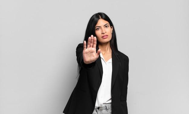 真面目で、厳しく、不機嫌で怒っている若いヒスパニック系実業家が、手のひらを開いてジェスチャーを止めている