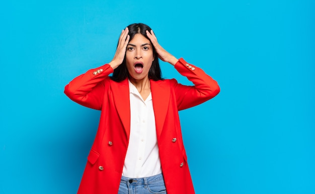 Young hispanic businesswoman looking unpleasantly shocked, scared or worried, mouth wide open and covering both ears with hands