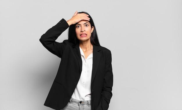 젊은 히스패닉 여성 사업가는 잊어버린 마감 시간에 당황하고 스트레스를 받고 혼란이나 실수를 덮어야 하는 상황에 직면해 있습니다.