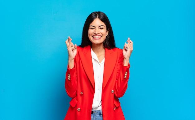若いヒスパニック系実業家は笑顔で心配そうに両指を交差させ、心配を感じ、幸運を願ったり期待したりします