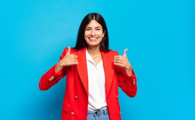 Молодой латиноамериканский бизнесвумен, широко улыбаясь, выглядит счастливым