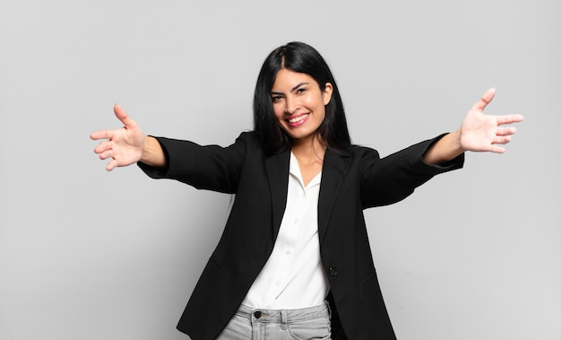 Young hispanic businesswoman smiling cheerfully giving a warm, friendly, loving welcome hug, feeling happy and adorable