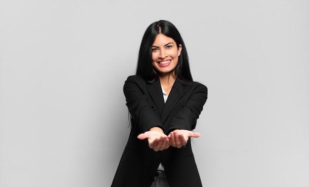 フレンドリーで自信に満ちたポジティブな表情で楽しそうに微笑むヒスパニック系の若いビジネスマンが、物やコンセプトを提供して見せる