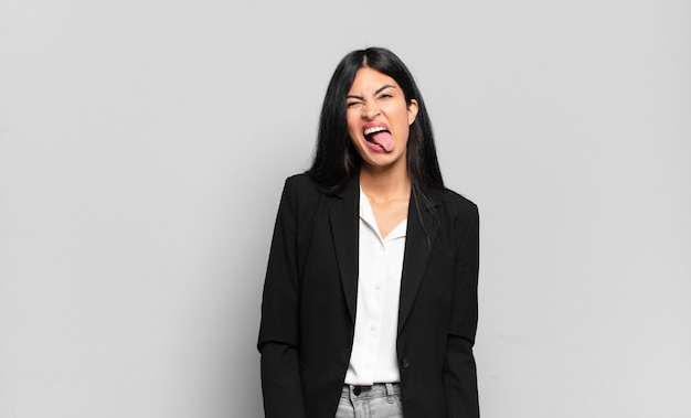 Young hispanic businesswoman with cheerful, carefree, rebellious attitude, joking and sticking tongue out, having fun
