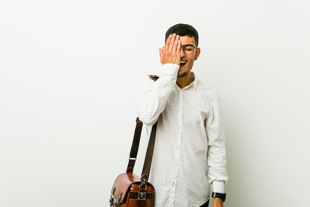 Young hispanic casual business man having fun covering half of face with palm.