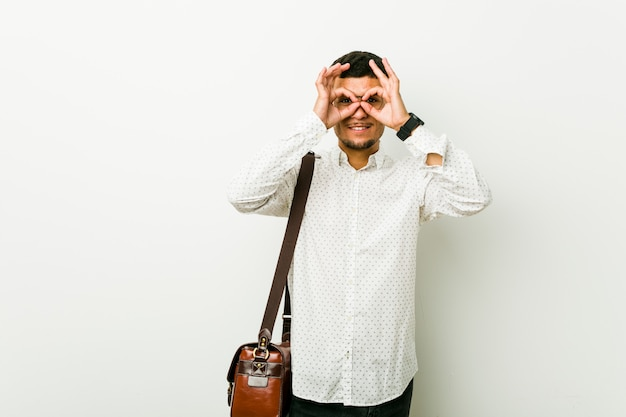 Young hispanic casual business man showing okay sign over eyes