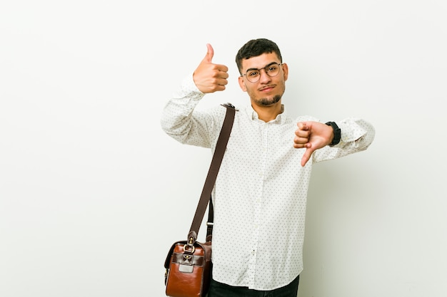 Young hispanic casual business man showing thumbs up and thumbs down, difficult choose