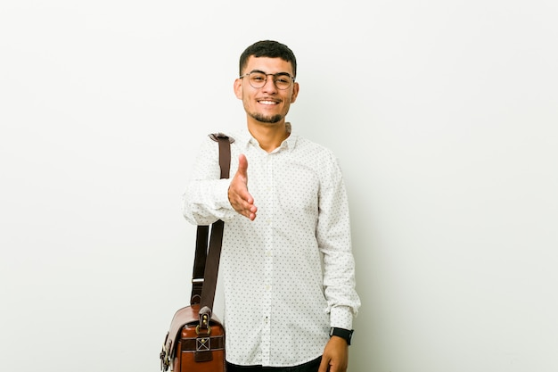 Young hispanic casual business man stretching hand in greeting gesture.