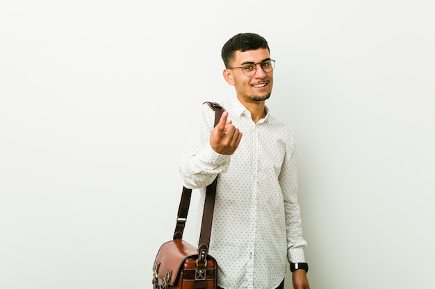Young hispanic casual businessman pointing with finger at you as if inviting come closer.