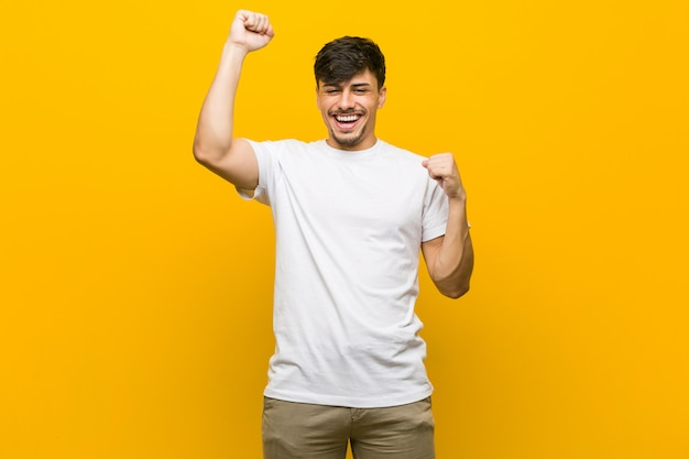 Young hispanic casual man celebrating a special day, jumps and raise arms with energy.