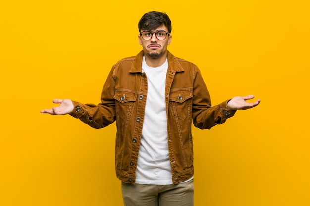 Young hispanic casual man doubting and shrugging shoulders in questioning gesture.