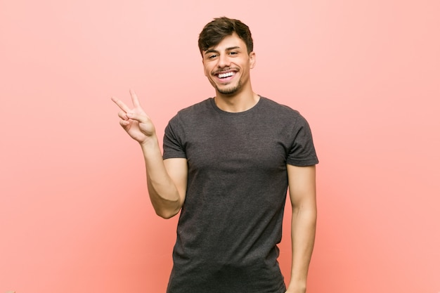 Young hispanic casual man joyful and carefree showing a peace symbol with fingers.