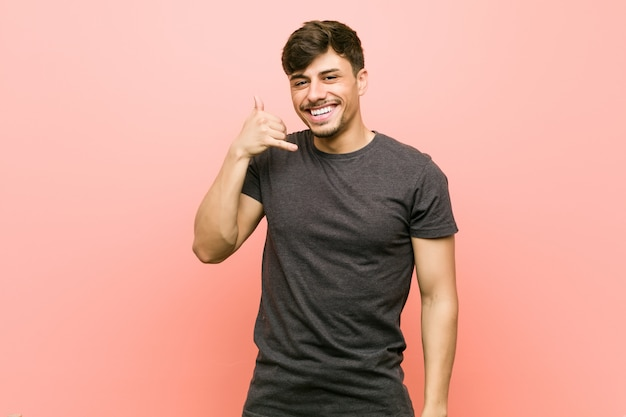 Young hispanic casual man showing a mobile phone call gesture with fingers.