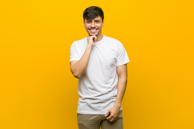 Young hispanic casual man smiling happy and confident, touching chin with hand.