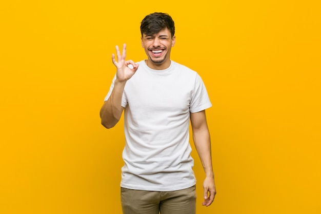 Young hispanic casual man winks an eye and holds an okay gesture with hand.