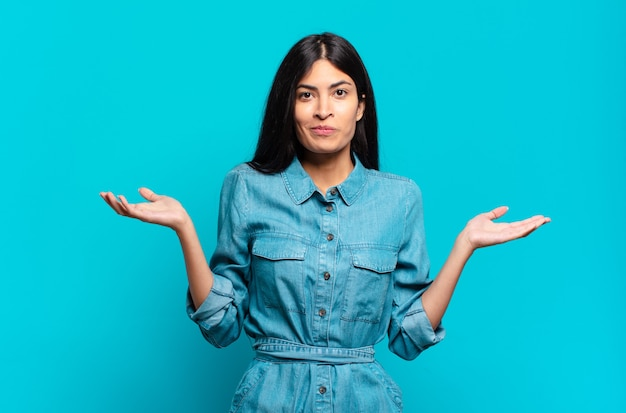 Young hispanic casual woman feeling puzzled and confused, doubting, weighting or choosing different options with funny expression