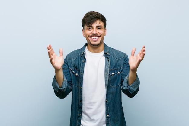 Молодой латиноамериканский крутой мужчина получил приятный сюрприз, взволновал и поднял руки.