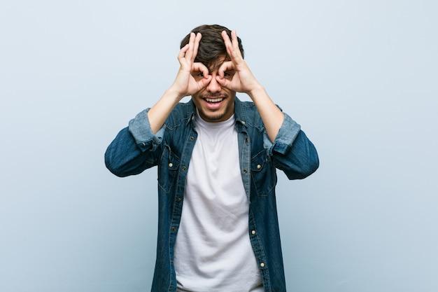 Young hispanic cool man showing okay sign over eyes