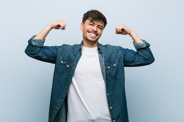 Young hispanic cool man showing strength gesture with arms, symbol of feminine power