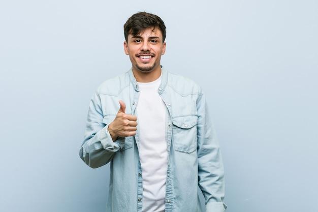 Young hispanic cool man smiling and raising thumb up