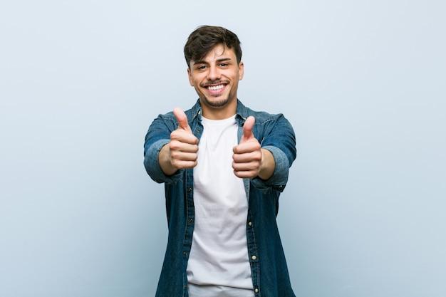 Молодой латиноамериканский крутой человек с большими пальцами руки вверх, приветствует что-то, поддерживает и уважает концепцию.