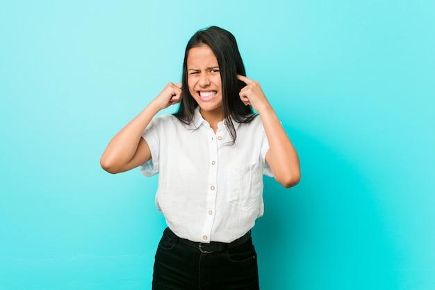 手で耳を覆う青い壁に対して若いヒスパニックのクールな女性。