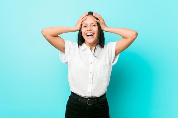 青い壁にヒスパニック系のクールな女性が笑いながら手を頭を抱えて笑います。幸福 。