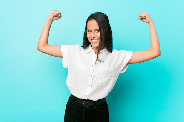 Молодая испанская холодная женщина против голубой стены показывая силу жест с оружием, символ женской силы