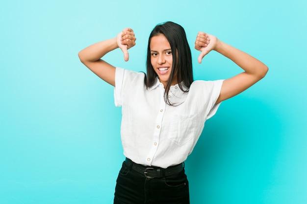 親指ダウンと嫌悪感を示す青い壁にヒスパニック系のクールな女性。
