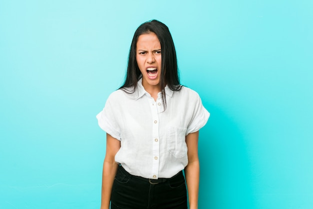 Young hispanic cool woman against a blue wall screaming very angry and aggressive.