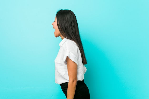 Young hispanic cool woman against a blue wall shouting towards