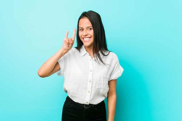 Young hispanic cool woman against a blue wall showing a horns gesture as a revolution concept.