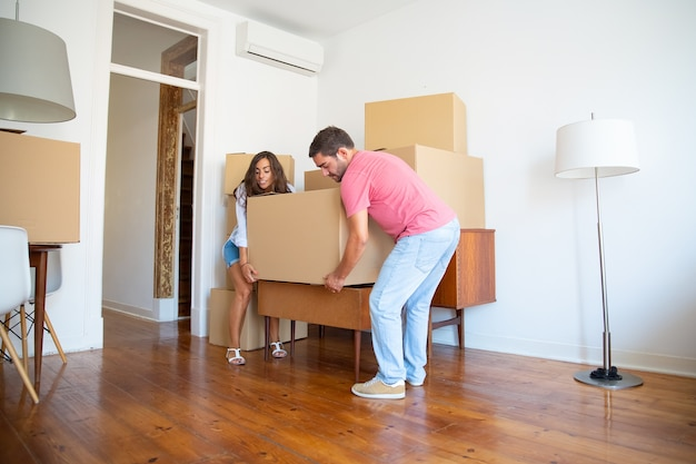 Young hispanic couple moving into new apartment, carrying carton boxes and furniture