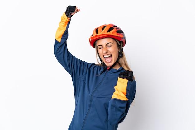 Молодая латиноамериканская женщина-велосипедист, изолированные на белом фоне, празднует победу