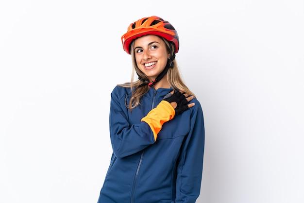 Молодая латиноамериканская женщина-велосипедист изолирована на белой стене, глядя вверх, улыбаясь
